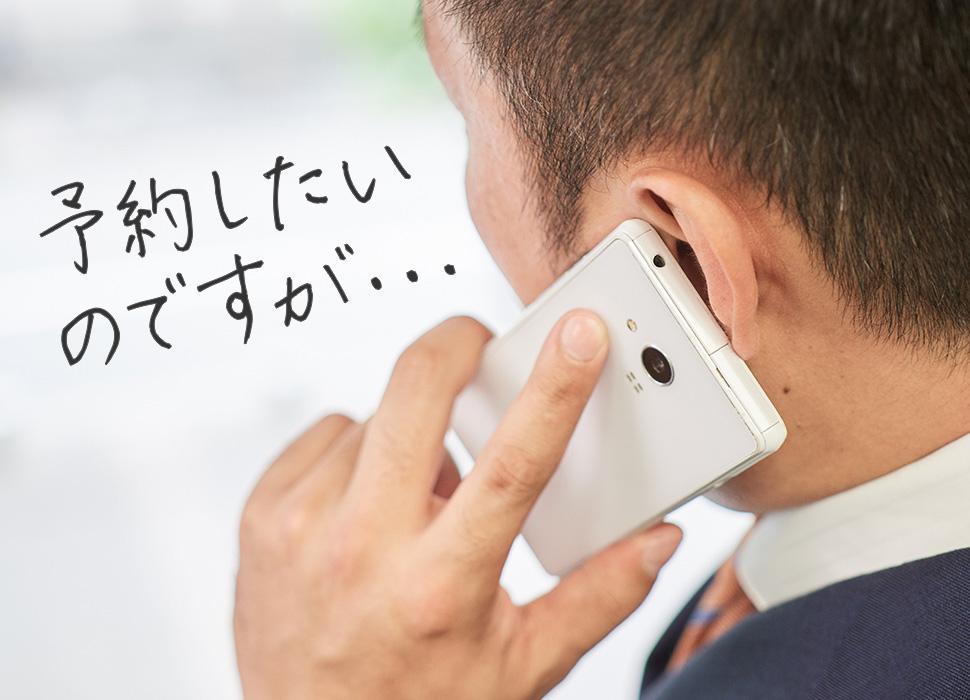 電話でクリニックの予約を行っている男性